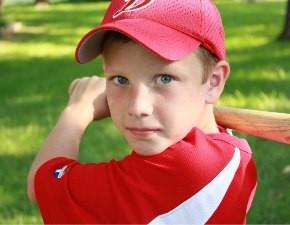 Мальчик в спортивной майке и бейсболке с бейсбольной битой на зелёном газоне