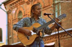 Бард Сергей Шпилевский поёт и играет на гитаре перед микрофоном