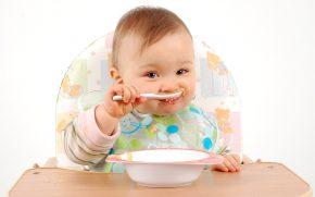 Ребёнок ест детскую еду ложкой изтарелки настуле застолом