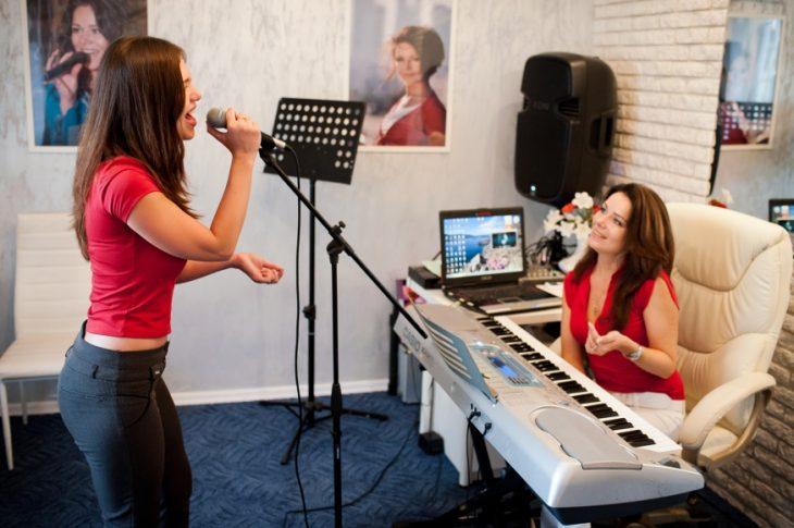 Занятия повокалу: комната, микрофон состойкой, MIDI-клавиатура, компьютер, ноты, колонки (сайт Минской школы киноискусства)