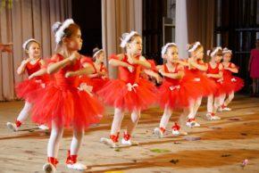 Девочки танцуют насцене вкрасных платьях ибелых колготках (фото)