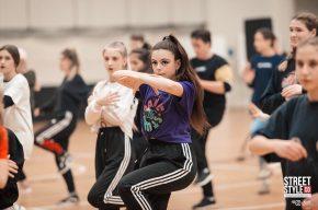 Девушка, педагог, в танцевальном классе, показывает танцевальные движения