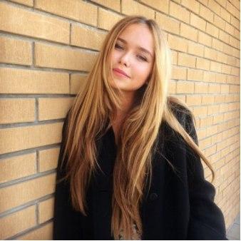 Длинноволосая девушка в чёрном пальто, прислонившаяся к жёлтой стене (кирпич или плитка)