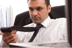 Мужчина в белой рубашке рассматривает тёмный галстук, сидя на кресле с пиджаком