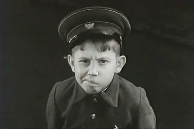 Мальчик в сюртуке с пуговицами, фуражке набекрень, с кривой улыбкой